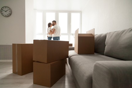 Cardboard boxes with kissing couple at background, moving day concept, young family belongings in new apartment, man and woman living together relocating, happy homeowners just moved into own home