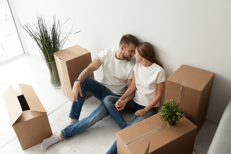 Young couple sitting on the floor with cardboard boxes bonding holding hands, happy man and woman enjoy moving day in new unfurnished rental bought apartment, homeowners relocation into own house Stock Photo