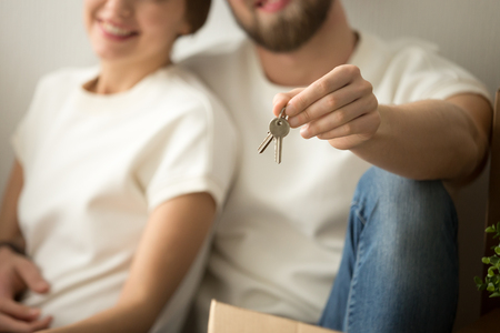 Happy new home owners couple holding house keys, smiling real estate buyers renters tenants made rental purchase deal, man showing apartment key on camera, property ownership concept, close up view Stock Photo