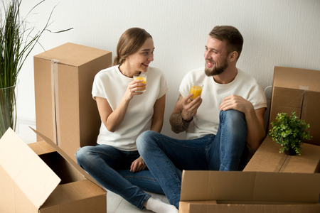 Young smiling couple just moved into new home having break drinking juice packing unpacking cardboard boxes, happy man and woman ready to relocate sitting on the floor with belongings on moving day Stock Photo