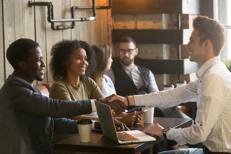 Gemischtrassiges Händeschütteln der afrikanischen und kaukasischen Männer bei der Sitzung im Café, verschiedene Freunde, die das Sitzen am Coffeeshoptisch oder an den schwarzen Paaren machen das Abkommen, das dem weißen Geschäftsmann mit Laptop Hände rüttelt, grüßen