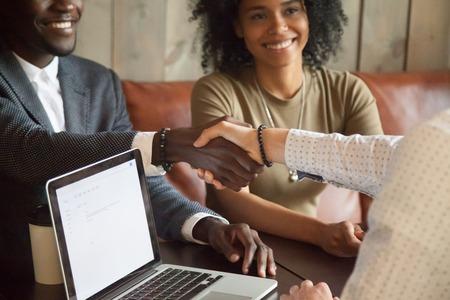 Szczęśliwa młoda para afroamerykanów robi transakcję uścisk dłoni kaukaski broker ubezpieczeniowy w kawiarni, czarny zadowolony klient i pośrednik w handlu nieruchomościami lub sprzedawca, ściskając ręce na spotkaniu w biurze z laptopem