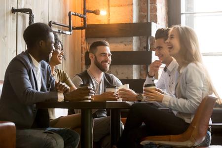 Amici multirazziali che si divertono e ridono bevendo caffè nella caffetteria, diversi giovani che parlano scherzando seduti insieme al tavolo del caffè, multi etnici che trascorrono del tempo in caffetteria