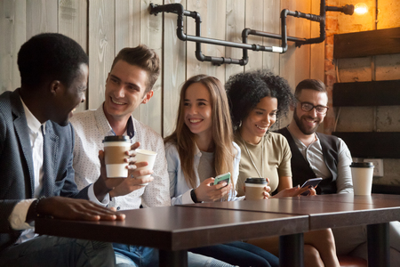 Happy multi ethnic group of friends talking using smartphones in cafe, diverse young people laughing having fun at coffee break in coffeehouse, cheerful millennials enjoying meeting in coffeeshop Stockfoto