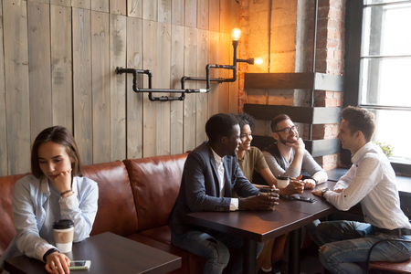 Diverse multiracial people hanging together in coffeehouse ignoring sad young girl sitting alone at cafe table, upset social outcast loner suffers from unfair attitude or discrimination among friends