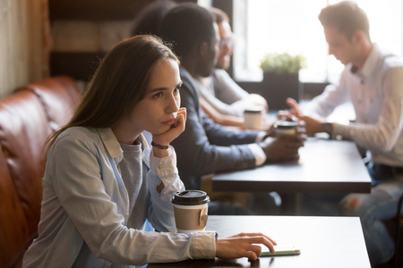 Pensive upset young rejected girl waiting for boyfriend to come on first date in cafe, frustrated social outcast or loner sitting alone at coffeeshop table with phone offended excluded by friends Stock Photo