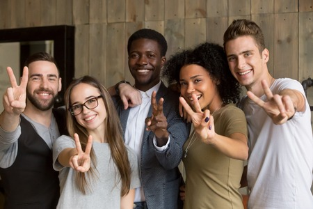 Happy multi ethnic young people looking at camera, smiling diverse friends or students showing peace sign, multicultural millennials posing together at meeting, tolerance and racial equality concept Stock Photo