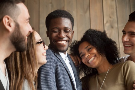 Happy diverse black and white people group with smiling faces bonding together, cheerful african and caucasian young multi ethnic friends having fun laughing embracing, multiracial friendship concept Stock Photo