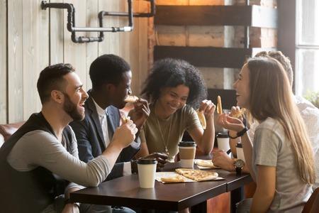 Gemischtrassige glückliche junge Leute, die Pizza in der Pizzeria, nette Schwarzweiss-Kameraden lachen essen, die Mahlzeit genießend haben den Spaß, der zusammen am Restauranttisch, verschiedene Freunde sitzt, teilen das Mittagessen bei der Sitzung Standard-Bild