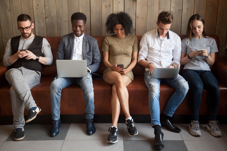 Multicultural young people using laptops and smartphones sitting in row, diverse african and caucasian millennials entertaining online obsessed with modern devices waiting in queue, gadget addiction Reklamní fotografie - 94771922