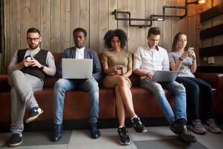 소파에 함께 앉아있는 다양한 젊은이들이 랩톱 및 스마트 폰, 디지털 라이프 및 가젯 사용 과용 개념을 사용하여 온라인, 아프리카 및 백인 밀레니엄