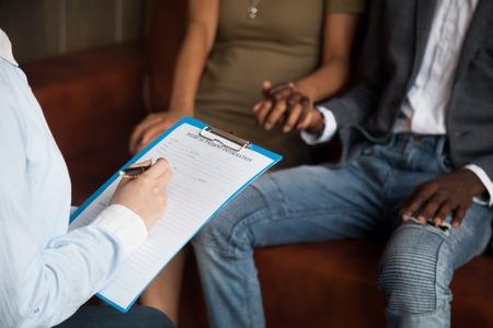 의사 또는 심리학자 작성 의료 환자 정보 양식 클립 보드를 들고 아프리카 계 미국인 부부, 결혼 상담, 가족 치료, 불임 개념에 대 한 불 임 치료 스톡 콘텐츠