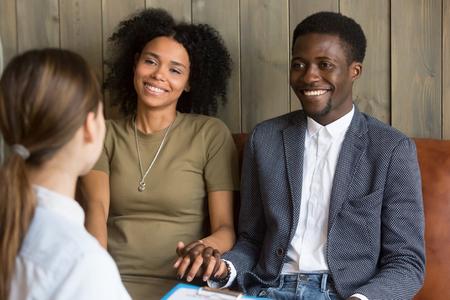 의사, 흑인 남편과 아내로부터 좋은 소식을 듣고 행복하게 손을 잡고 아프리카 계 미국인 젊은 부부는 가족 회의 권고를 듣고 치료 세션 중 화해 후에