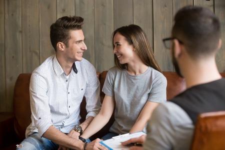 행복 한 젊은 조정 된 부부 심리학자, 심리학자와 치료 세션에서 위로, 안심 웃 고 남편과 아내 손, 효과적인 가족 상담 또는 관계 충돌 해결 개념