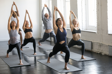 Group of young sporty people practicing yoga lesson with instructor, stretching in Warrior one exercise, Virabhadrasana 1 pose, working out, indoor full length, studio Reklamní fotografie