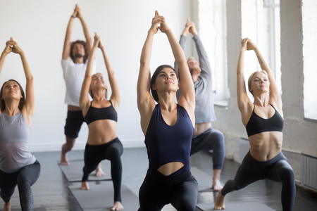 Group of young sporty people practicing yoga lesson with instructor, stretching in Warrior one exercise, Virabhadrasana 1 pose, working out, indoor close up, students training in club, studio