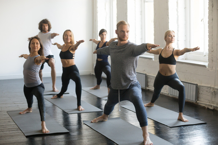 Group of young sporty people practicing yoga lesson with instructor, stretching in Warrior Two exercise, Virabhadrasana 2 pose, working out, indoor full length, students training in club, studio 版權商用圖片 - 94827606