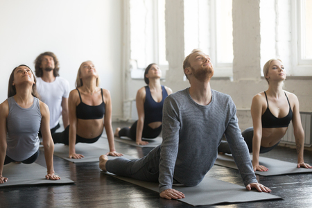 Group of young sporty people practicing yoga lesson with instructor, stretching in upward facing dog exercise, Urdhva mukha shvanasana pose, working out, indoor full length, students training, studio