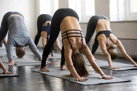 Group of young sporty people practicing yoga lesson with instructor, stretching in Downward facing dog exercise, adho mukha svanasana pose, working out, indoor full length, students training, studio