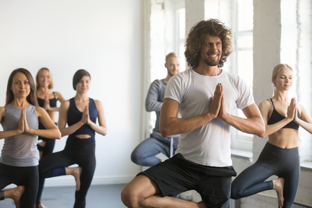 Group of young sporty people practicing yoga lesson with instructor, standing in Vrksasana exercise, Tree pose, working out, indoor close up, students training in club, studio Stock Photo