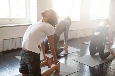 Group of young sporty people practicing yoga lesson with instructor, stretching in Ustrasana exercise, Camel pose, working out, indoor full length, students training in club, studio