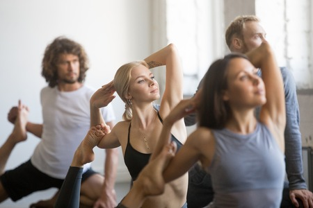 Group of young sporty people practicing yoga lesson with instructor, stretching in Mermaid exercise, Eka Pada Rajakapotasana pose, working out, indoor close up, students training in club, studio Stock Photo