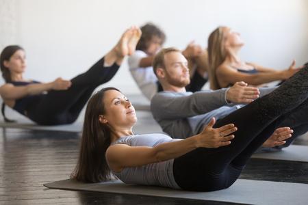 Grupa młodych sportowców ćwiczących lekcje fitness z instruktorem