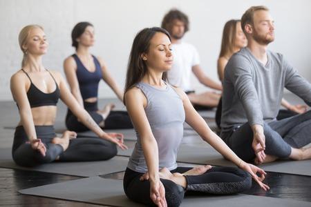 Grupo de jóvenes deportistas practicando clase de yoga con instructor, sentado en ejercicio de Padmasana, postura de loto, ejercicio, interior de cuerpo entero, entrenamiento de estudiantes en club, estudio