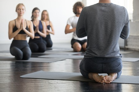 Group of young sporty people practicing yoga with instructor