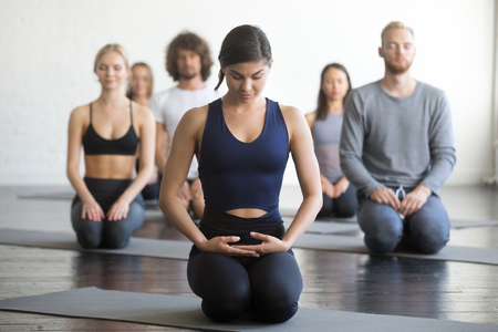 Group of young sporty people practicing yoga lesson with instructor, sitting in vajrasana pose, working out, indoor full length, students training in club, studio. Stock Photo