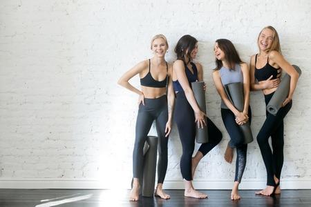 白い壁に立っているヨガマットを持つ若いスポーティな女の子のグループ。