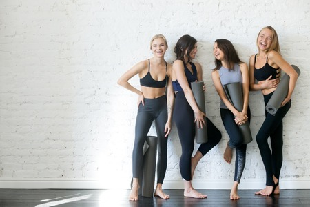 Group of young sporty girls with yoga mats standing at white wall. Stockfoto