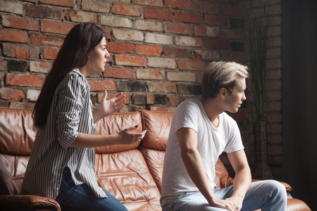 Unhappy couple arguing, young woman talking telling arguments apologizing man feels offended in dispute fight conflict, wife trying to make peace asking jealous stubborn husband for forgiveness