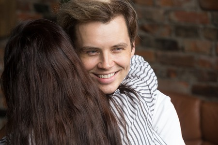 Young sly liar man happily smiling while woman embracing him, dishonest cheating boyfriend womanizer hiding grin hugging naive girlfriend, insincere husband deceiving wife showing fake feelings Foto de archivo