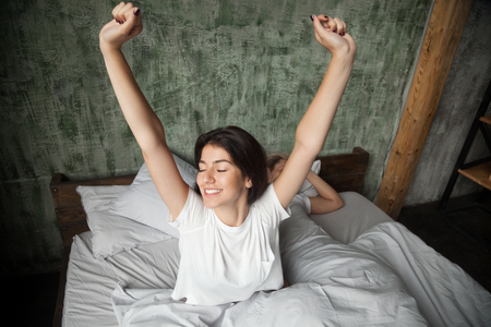Young smiling woman waking up happy after healthy sleep stretching on comfortable bed with sleeping man at background, rested refreshed girl enjoys pleasant wakeup, good morning in cozy loft bedroom Stock Photo