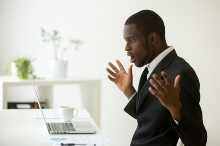 Shocked african-american businessman in suit feeling stunned by online news looking at computer screen sitting at workplace with laptop, stressed trader investor surprised by stock market changes