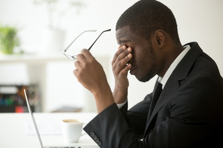 Der afrikanische Geschäftsmann des Computers, der Gläser entfernt, glaubt Augenbelastungsermüdung nach langer Büroarbeit über Laptop, erschöpfter überarbeiteter betonter deprimierter schwarzer Mann, der Visionsproblem des schlechten Anblicks hat Standard-Bild