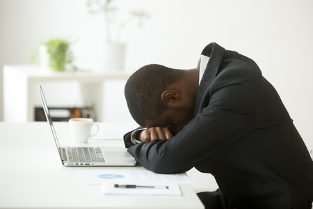 African-american tired deprived businessman feeling lack of sleep having nap at workplace, black restless entrepreneur hopeless by bankruptcy or debt, depressed investor desperate about failure