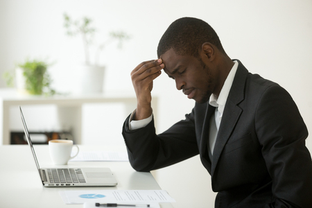 Headache at work concept, stressed african-american businessman feels strong sudden migraine working on laptop at workplace, frustrated dizzy black man in suit touching head tired of chronic fatigue Banque d'images