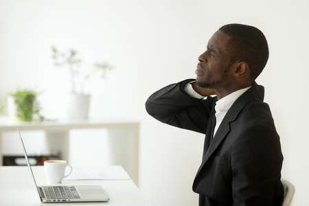 African american businessman feels neck pain sitting on uncomfortable office chair at work, black man having computer syndrome suffering from stiff neck shoulder ache joint pain after sedentary work