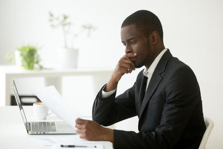 Ernstige Afro-Amerikaanse zakenman werkgever denken aan zakelijke aanbieding lezen sollicitatiebrief op werkplek, verbaasd zwart bedrijf executive kijken naar financieel document rekening houdend met contract Stockfoto