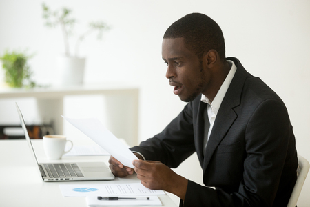 Shocked african-american businessman in suit surprised by reading mail paper letter holding notification sitting at workplace, amazed confused black employee astonished by unexpected notice