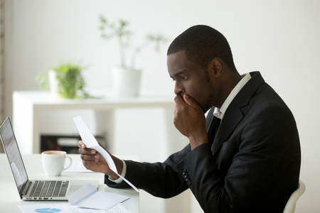 Shocked african-american businessman frustrated by notification about loan debt, confused stunned black employee feeling stressed reading unexpected bad news in letter, got dismissed fired in notice Banco de Imagens