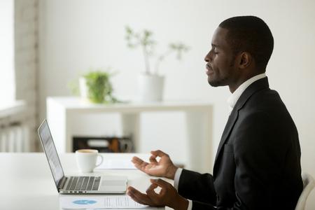 Tranquilo empresario afroamericano pacífico en traje meditando en la oficina, ejecutivo empleado negro practicando yoga en el lugar de trabajo para el equilibrio mental emocional, sin estrés en el trabajo, alivio libre, vista lateral