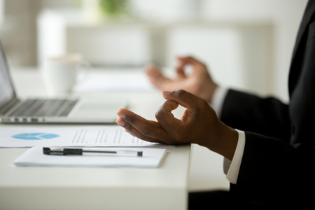 African american calm businessman relaxing meditating in office, peaceful ceo in suit practicing yoga at work, focus on black man hands in mudra, successful mindful people habits concept, close up Stock Photo