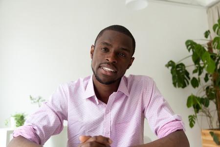 Hombre afroamericano hablando mirando a cámara, candidato a vacante de hombre negro haciendo videollamada para entrevista de trabajo a distancia, videoblog de grabación de vlogger de piel oscura, vista desde la cámara web, retrato en la cabeza