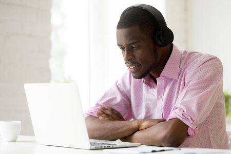 African american man wearing headphones using laptop looking at computer screen, smiling young black businessman learning studying online, watching video or making call with pc internet application