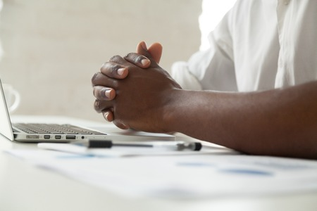 Clasped male black hands on office desk close up view, attentive african american businessman in closed posture, tension or nervous anticipation, determination, thinking of business decision concept