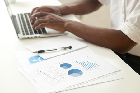Data analysis and business statistics concept, african-american businessman using laptop analyzing work result infographic stats graphs and charts, making report or strategic planning, close up view Stock Photo
