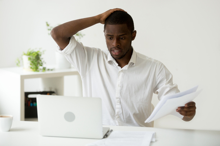 Confused african-american businessman having problem with documents looking at laptop at work, frustrated black employee stressed by mistake or unexpected computer error crash, forgot about deadline
